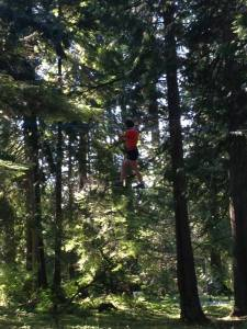 Yes that is actually me in a harness extremely high in the trees on a single wire. Not my favorite experience.